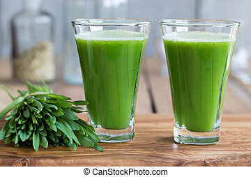 Two green barley grass shots on a wooden background - Two...