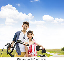 happy father with daughter riding bicycle  outdoors happy father with daughter riding bicycle  outdoors