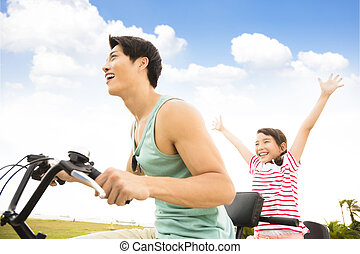 happy father with daughter riding bicycle  outdoors