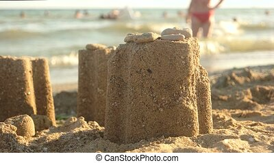 Sand tower and rocks. Small sandcastle and sunlight.
