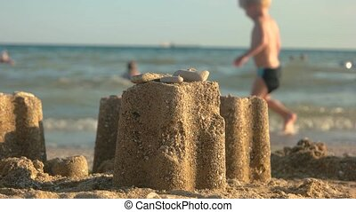 Sand tower close up. Sandcastle, blurred beach background.