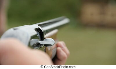 Skeet shooting from a shotgun with flying away green...