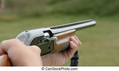 Skeet shooting shotgun aiming and shooting in a field in autumn in slow motion