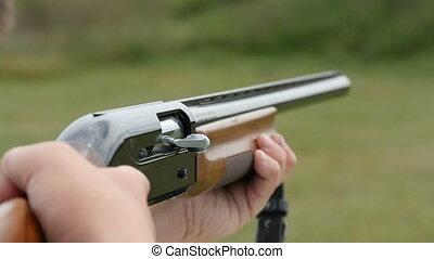 Skeet shooting shotgun aiming and shooting in a field in...