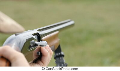 Some man aiming and shooting from a hunting rifle in a field in slow motion