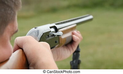 Man trains skeet shooting, while aiming somewhere from his...