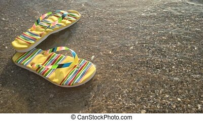 Floating flip flops and sunlight. Sea water in motion....
