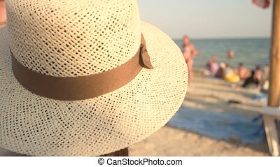 Woman in hat, blurred seashore. Lady near sea. The summer...