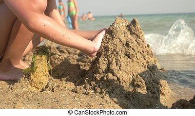 Kid building a sand tower. Child playing near the sea.