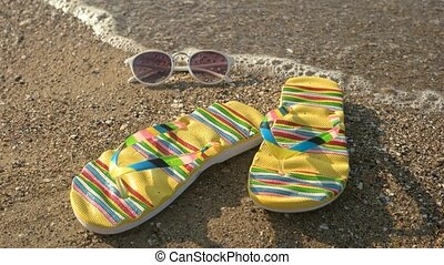 Flip flops and sunglasses. Footwear on the shore. Hear the...