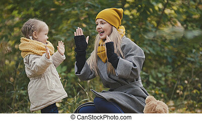 Woman with daughter little girl plays in autumn park