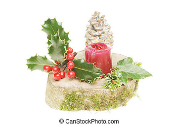Yule log with holly,ivy,pine cone and a burning candle