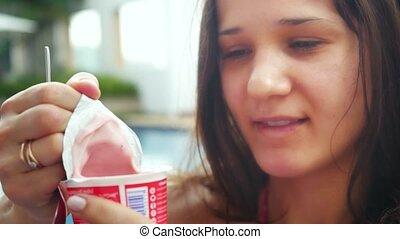 Young beautiful woman enjoying and eating yogurt outdoors...