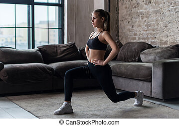 Pretty fit woman doing frontal lunges or squat exercise...