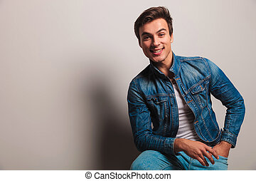 happy casual young man sitting on chair and smiles to the...