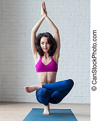 Cute skinny young woman doing toe stand balance posture...