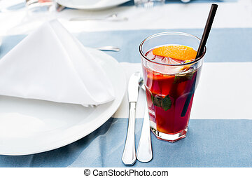 Bright red lemonade cocktail with raspberry garnish with lemon, berries and mint on table