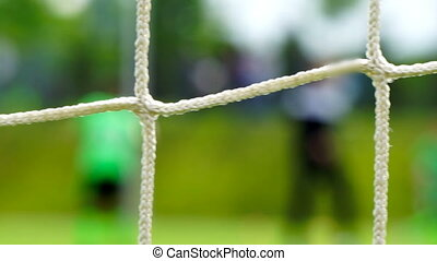 Soccer game seen through net, blurred view