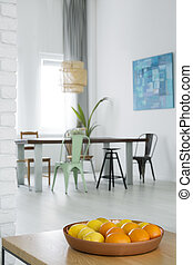White dining room with communal table, chairs and trendy...