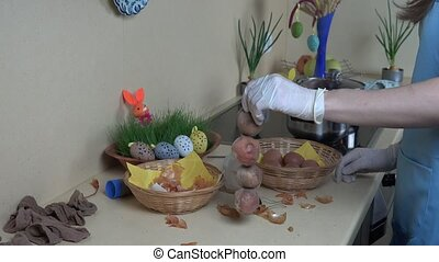 hands with gloves put eggs wrapped in sock into boiling pot water with paint