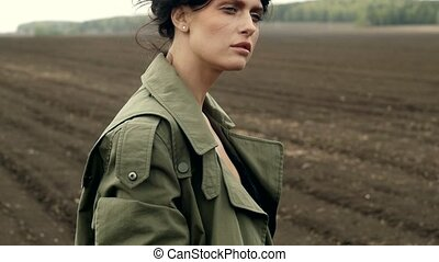 Woman in khaki coat posing on field - Young brunette wearing...