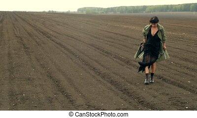 Woman walking on field - Woman in dress and coat walking in...