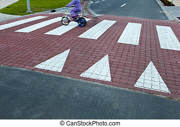 father with a small girl on a bike crossing a street (motion...