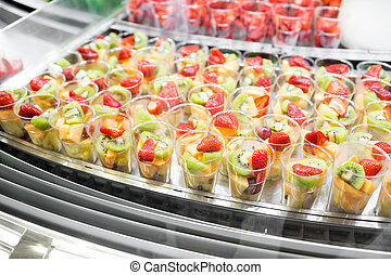 Fruit salad arranged in plastic cups for sale. refrigerator...