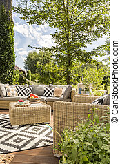 Outdoor terrace with rattan furnitures and accessories in...