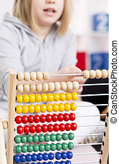 Girl learning to count using abacus