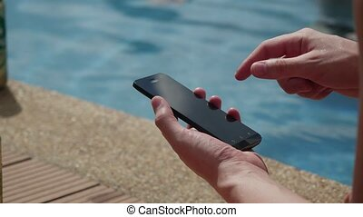 Close-Up Businessman using smartphone sitting by pool in...
