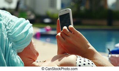Upset woman using smartphone lying on sunbed by pool....