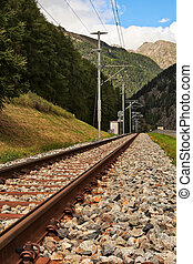 Railway tracks in mountains with forest on left side.