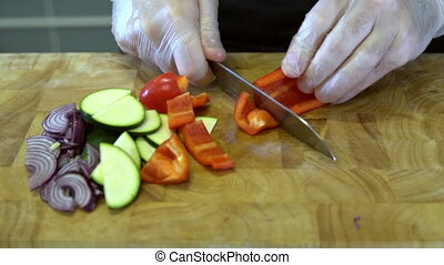 the chef slices bell pepper. Slow motion - the chef slices...