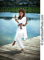 young woman in white practice yoga by the lake - young woman...