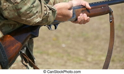Man shoots and reloads a shotgun while pulling back a breechlock in slow motion