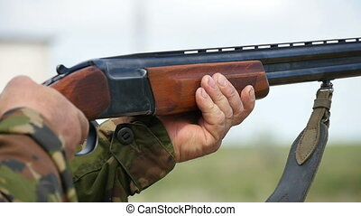 Skeet shooting shotgun aiming and shooting somewhere in autumn in slow motion