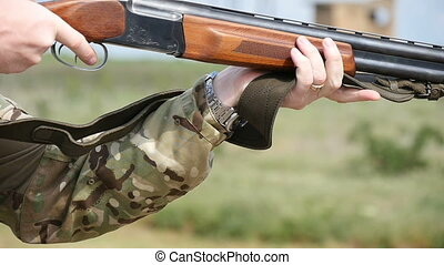 Man pulls a trigger and shoots from a double barrel shotgun in a field in slo-mo