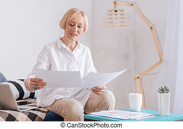 Attentive senior businesswoman checking documents - All in...