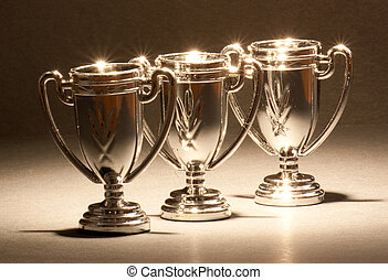 Three Trophies - Three shiny trophies standing in a row