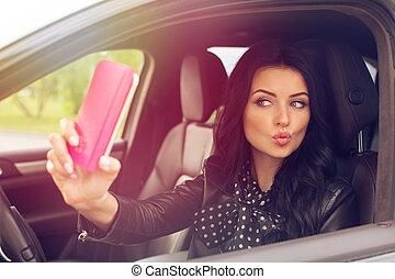 Beautiful brunette woman doing selfie in the car