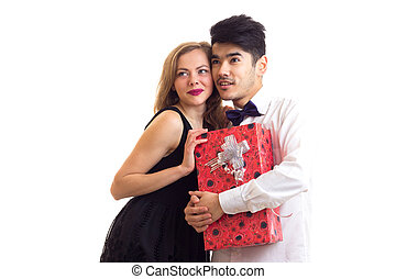 Young couple holding a present - Young handsome man with...