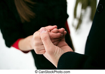 young couple tenderly holding hands. hands closeup
