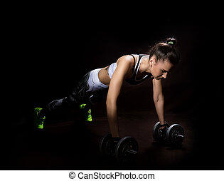 Fitness sexy girl on a dark background. Athlete doing exercises in the gym