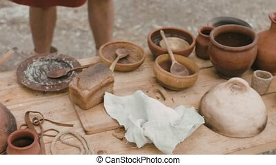 Dinner from pottery stands on the wooden table outdoors -...