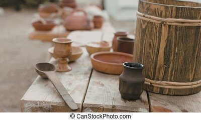 Ancient wooden and clay dishes left on the table after...
