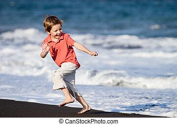 Kid Runs On The Beach - Boy running on black sand beach in...