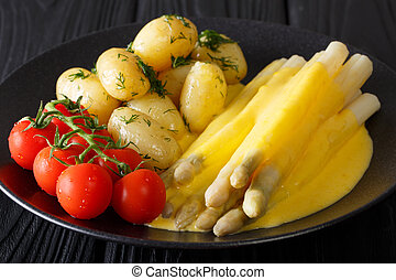 Asparagus with hollandaise sauce, new potatoes, greens and...