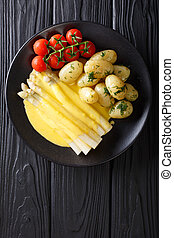 asparagus served with hollandaise sauce, new potatoes and...