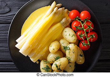 Tasty asparagus with hollandaise sauce and potatoes close-up...
